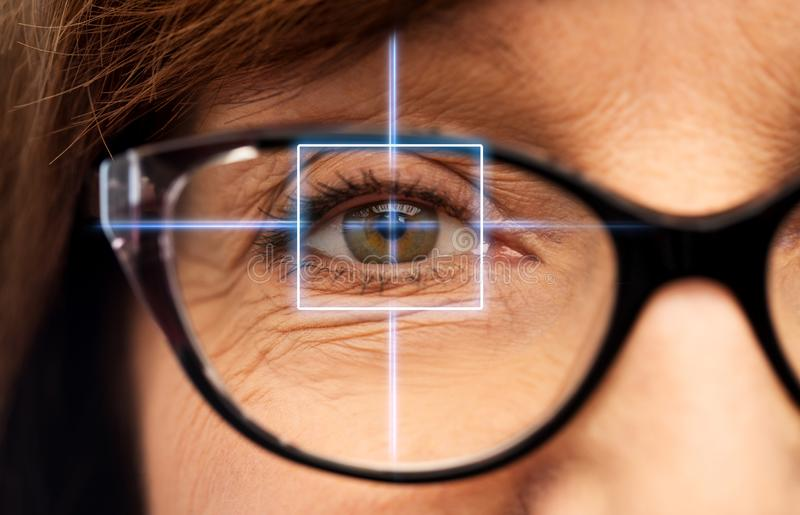 Close up of senior woman eye with laser light. Vision, eye surgery and ophthalmology concept - close up of face of senior woman in glasses with laser light royalty free stock photo