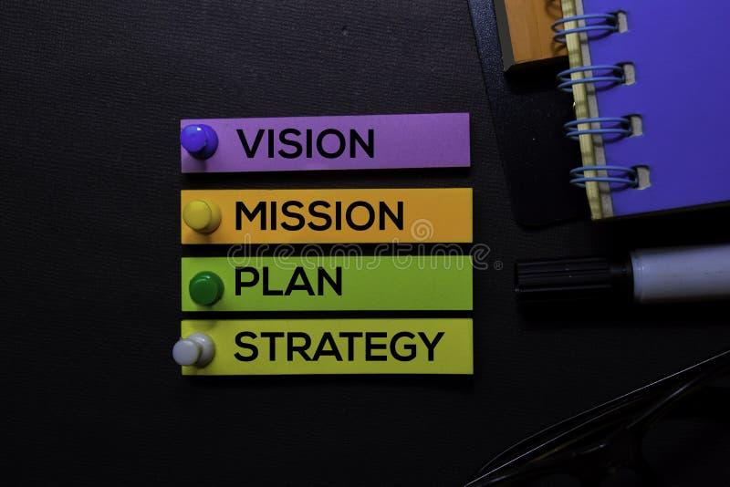 Vision, mission, plan, texte de stratégie sur les notes collantes d'isolement sur le bureau noir Concept de stratégie de mécanism photographie stock