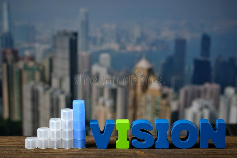 VISION text and graph on top wooden working table with city city. VISION text and graph on top wooden working table with city and office building background royalty free stock photo