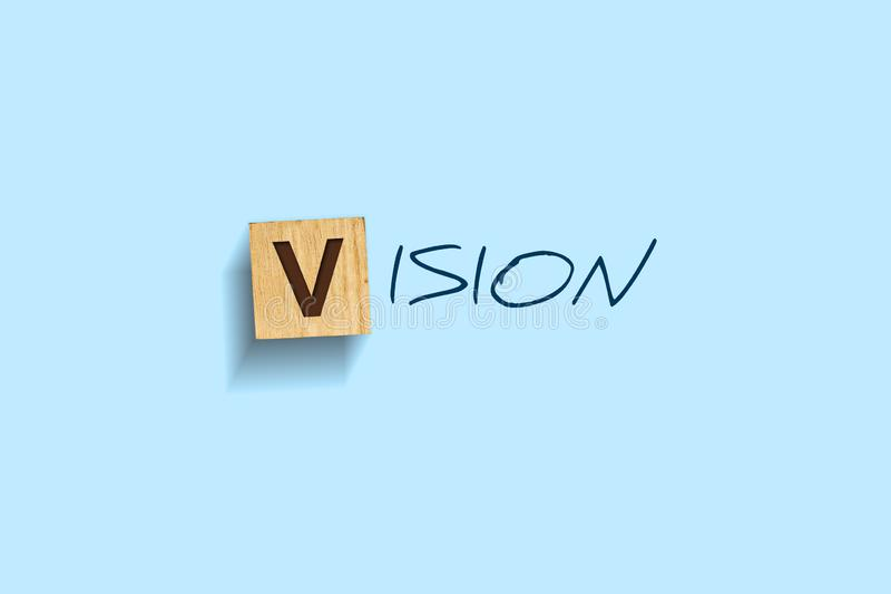 Vision. Words written on a wooden block. Blue background. Isolated. Business concept. stock photos
