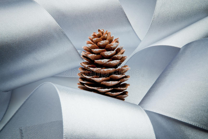 Visionary christmas. Representation of christmas tree in the snow made with blue ribbon and a pine cone stock photography