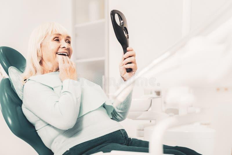 Visionnement de vieille dame ses nouvelles dents photographie stock