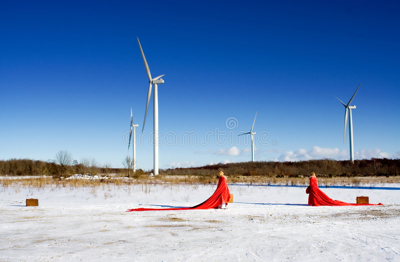 Visit. Red ladies on snow field with windmills stock photos