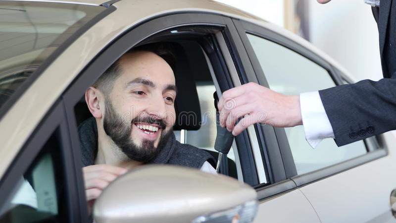 Visit the showroom. Young man gets hold car keys, looking at the camera and smiling, sitting in his new car stock photography