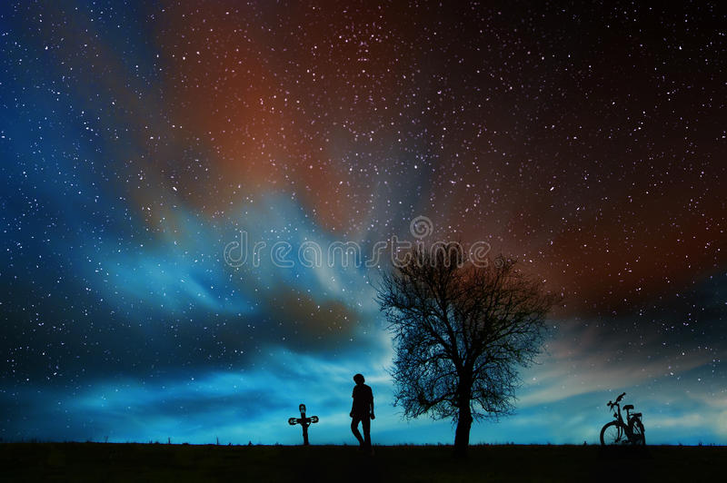 The visit. Silhouette of a man visiting a loved one`s grave at night against beautiful starry sky