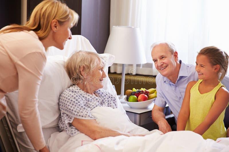 Visita de la familia a la abuela en cama de hospital fotos de archivo libres de regalías