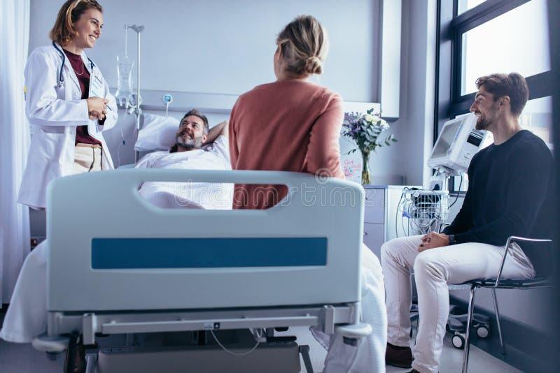 Visita degli amici e della famiglia paziente e parlare con medico immagine stock