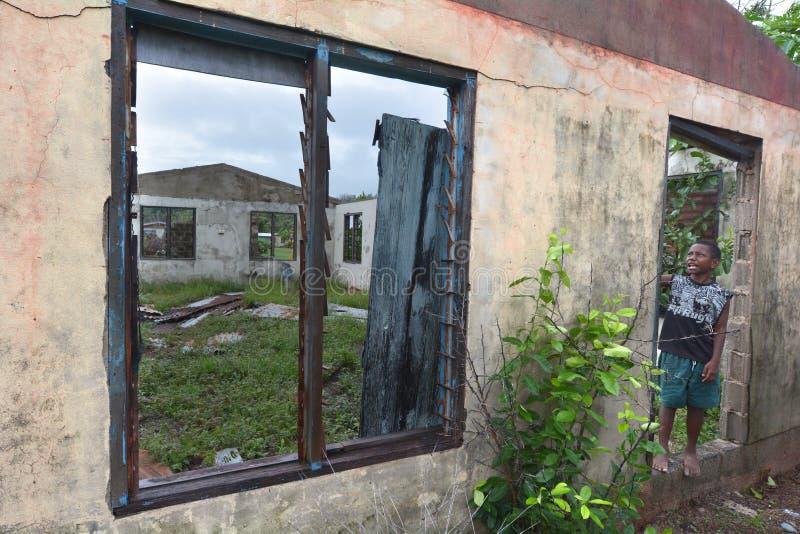 Visita nativa do menino do Fijian sua casa destruída pelo s tropical fotografia de stock royalty free