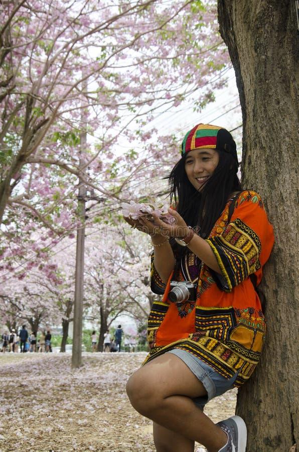 Visita tailandesa de la mujer de los viajeros asiáticos y el sostenerse flor a mano imagen de archivo