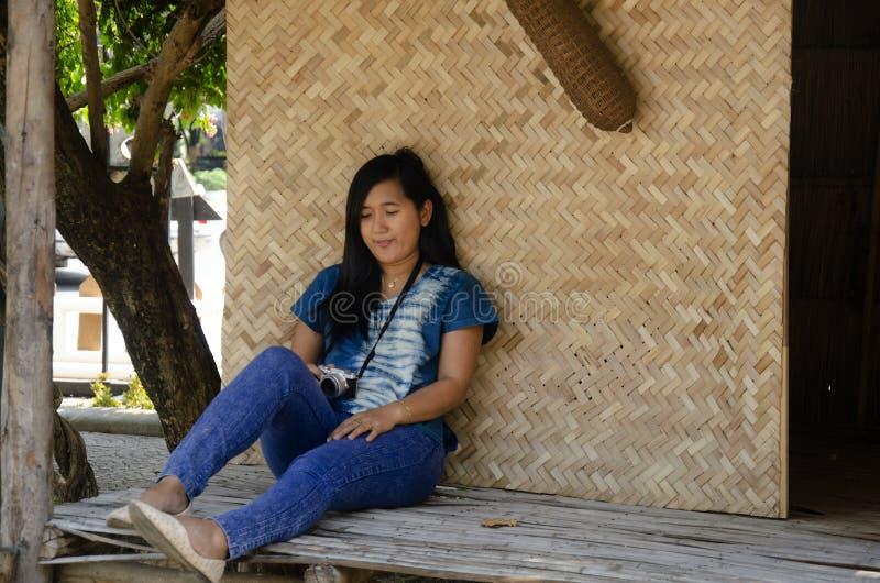 Visita tailandese di viaggio della donna dell'Asia e sedersi sul patio della capanna della paglia e del bambù che posa per la fot fotografia stock