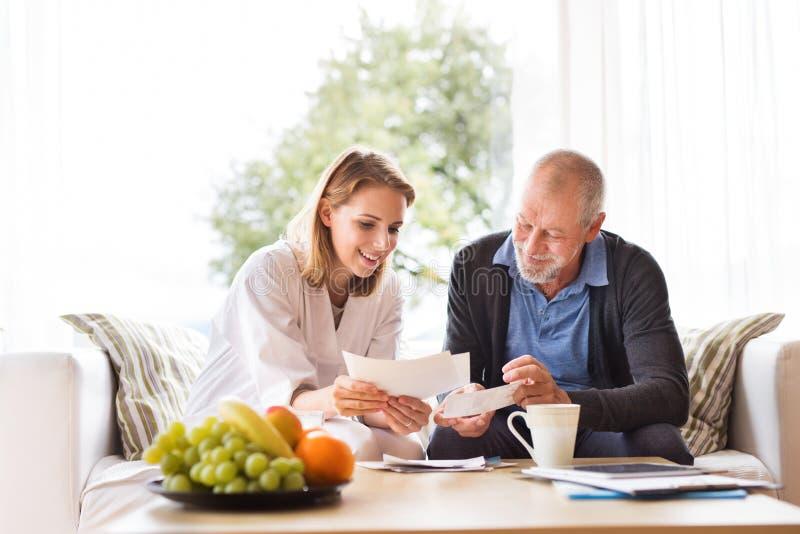 Visitante da saúde e um homem superior com a tabuleta durante a visita home fotos de stock royalty free