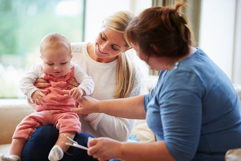 Visitante da saúde que fala à mãe com bebê novo fotografia de stock royalty free