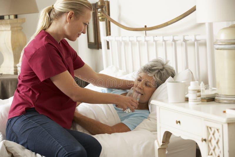 Visitante de la salud que da el vidrio mayor de la mujer de agua en cama en casa imagen de archivo