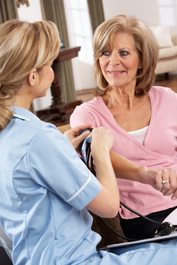 Visitante de la salud que toma la presión arterial de la mujer foto de archivo