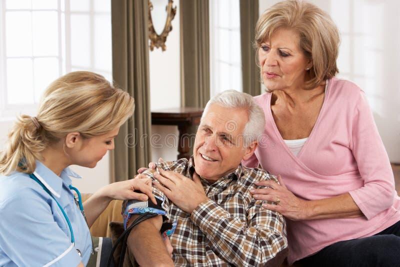 Visitante de la salud que toma la presión arterial del hombre mayor foto de archivo
