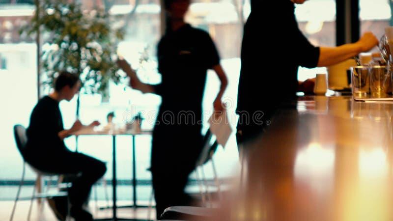 Visitante Defocused que usa seus smartphone e garçons no trabalho em um café moderno imagem de stock royalty free