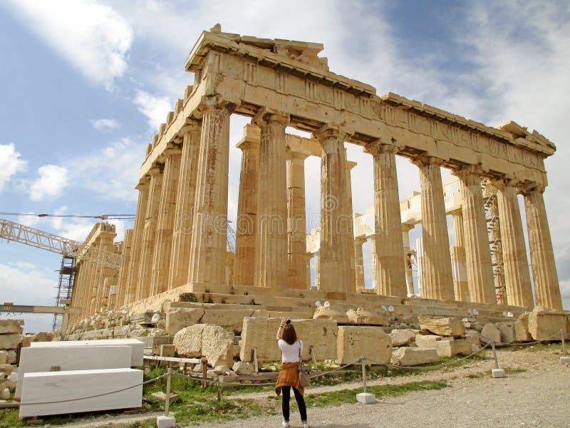 Visitante femenino que toma la foto del templo del griego clásico del Parthenon en la cumbre de la acrópolis, Atenas, Grecia fotografía de archivo