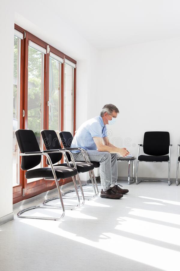 Visitante ou doente com máscara cirúrgica devido ao coronavírus sentado numa sala de espera vazia imagem de stock