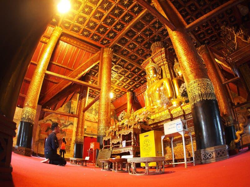 Visitante que reza dentro da pintura mural famosa da TAILÂNDIA do norte WAT PHUMIN imagem de stock royalty free