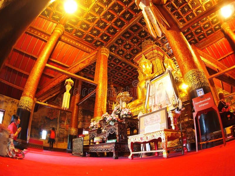Visitante que reza dentro da pintura mural famosa da TAILÂNDIA do norte WAT PHUMIN foto de stock royalty free