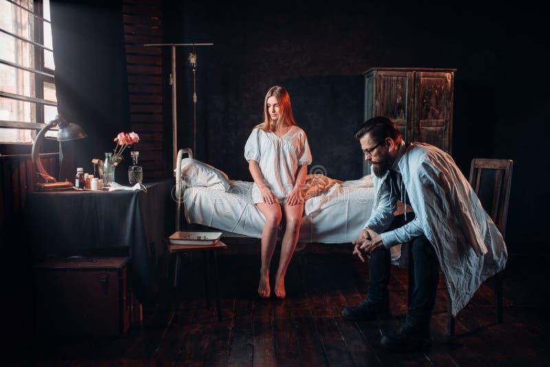Visitante que se sienta contra mujer enferma en cama de hospital fotografía de archivo libre de regalías