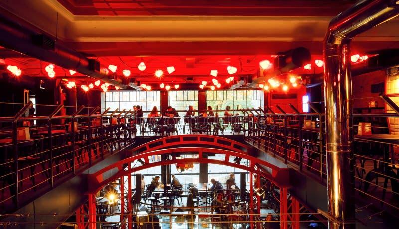 Visitantes de la tarde que se sientan dentro del espacio de la luz roja de la barra moderna de la ciudad imagen de archivo libre de regalías