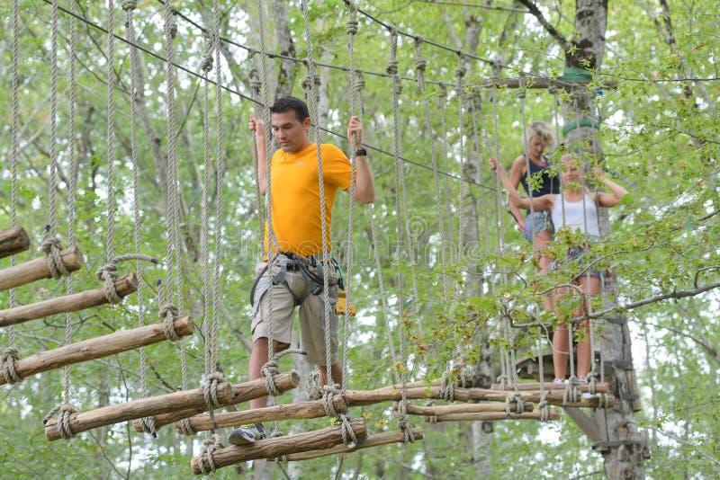 Visitantes en parque de la aventura en el puente de cuerda foto de archivo