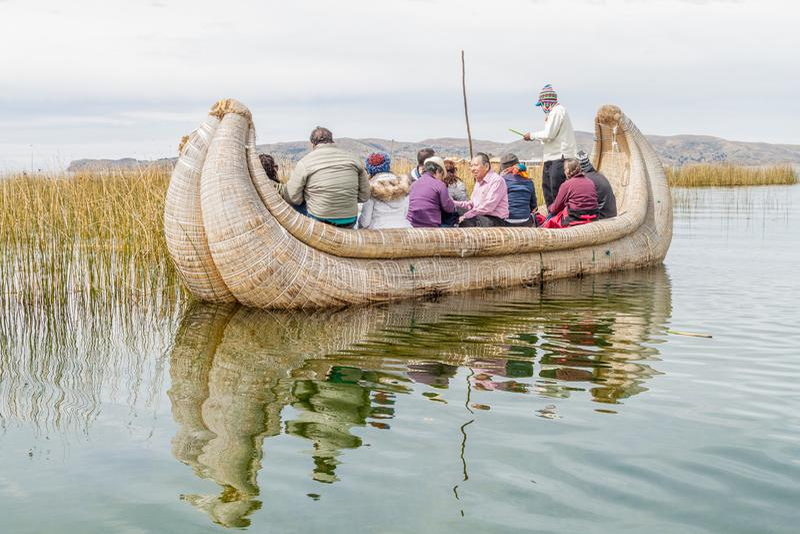 Visitantes en un barco de lámina cerca de las islas flotantes de Uros imagenes de archivo