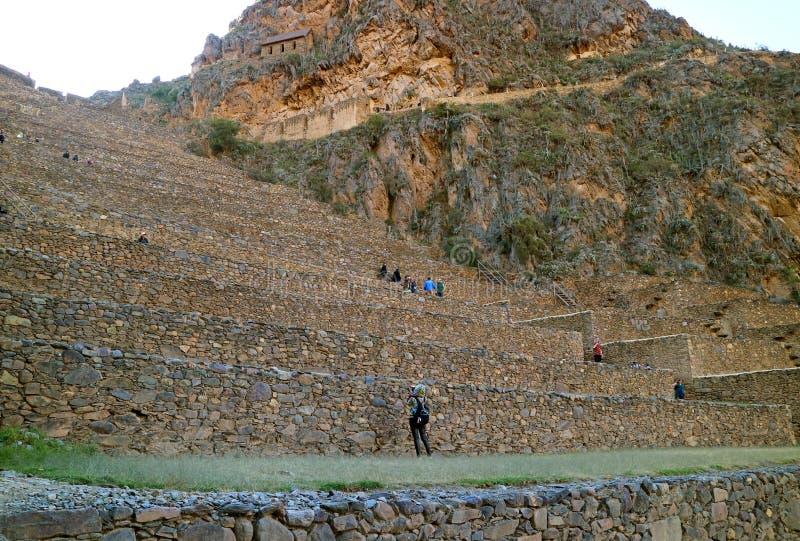 Visitantes femeninos que toman la foto de Ollantaytambo Inca Fortress Ruins, Urubamba, Cusco, Perú foto de archivo