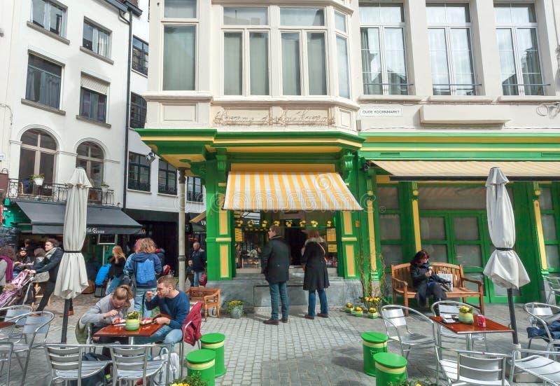 Visitantes hambrientos de la comida rápida al aire libre de la consumición del café y relajación en las pequeñas tablas del metal foto de archivo libre de regalías