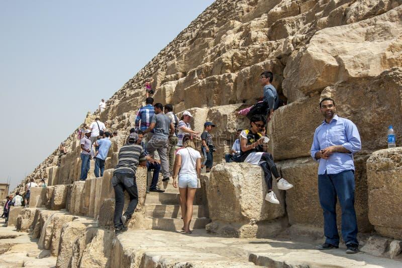 Visitantes a las pirámides de Giza en El Cairo en la subida de Egipto sobre los bloques enormes de la piedra arenisca de la pirám imagenes de archivo
