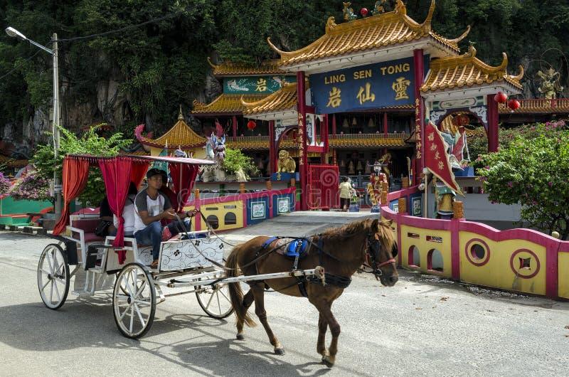 Visitantes não identificados no treinador do cavalo que passa pela entrada de Ling Sen Tong, caverna do templo, Ipoh, Malásia imagens de stock royalty free