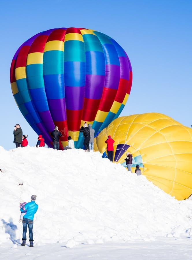 Visitantes que apreciam a vista dos balões de ar quente que inflam e que preparam-se para decolar foto de stock