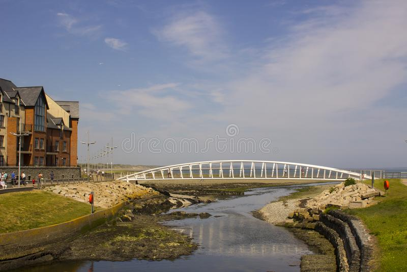 Visitantes que cruzam o passadiço moderno na boca do rio de Shimna na frente marítima no condado para baixo Irlanda do Norte de N foto de stock royalty free