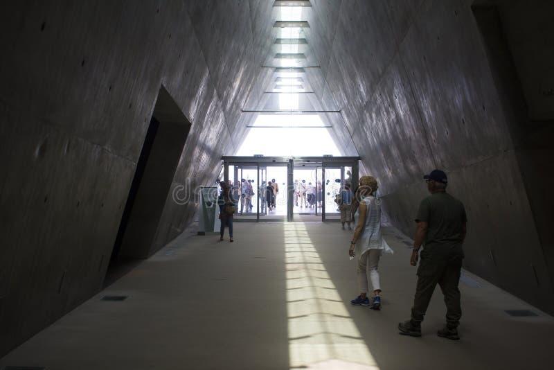 Visitantes que deixam a escuridão do museu de Yad Vashem no Jerusalém Israel e que movem-se na luz brilhante do dia imagens de stock