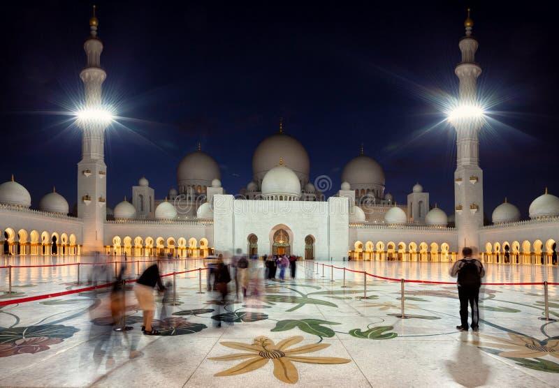 Visitantes que entran en la mezquita magnífica de Zayed en Abu Dhabi de emiratos en la oscuridad foto de archivo libre de regalías