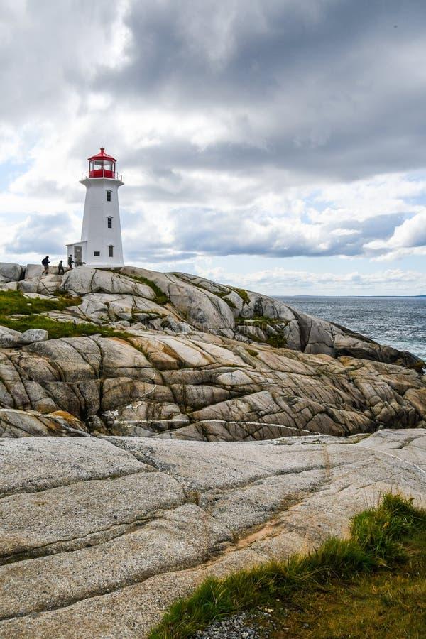 Visitantes que escalam ao farol da angra do ` s de Peggy em Nova Scotia foto de stock