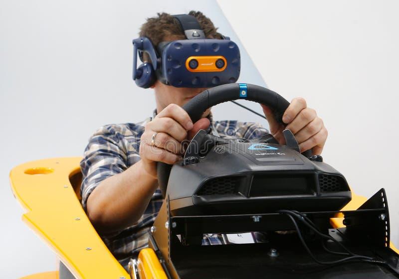 Visitantes que prueban experiencia de conducción de VR F1 en el modelo de McLaren en la cabina del htc de Vive en MWC 2019 imágenes de archivo libres de regalías
