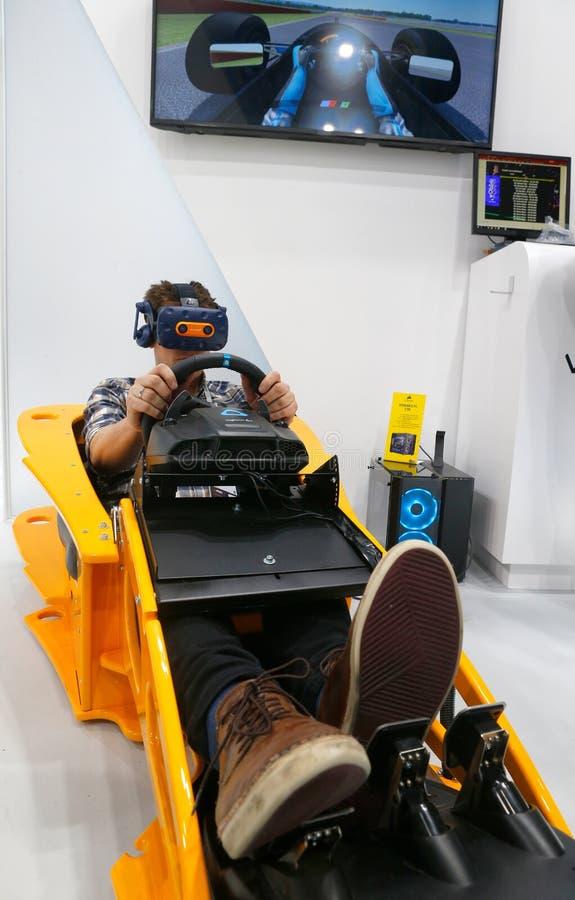 Visitantes que prueban experiencia de conducción de VR F1 en el modelo de McLaren en la cabina del htc de Vive en vertical de MWC fotos de archivo libres de regalías