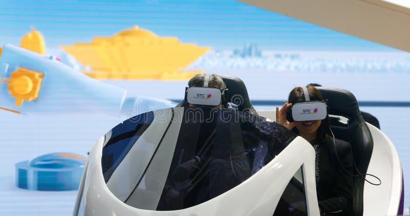 Visitantes que prueban experiencia del abejón de VR en la cabina de la STC en MWC 2019 fotografía de archivo