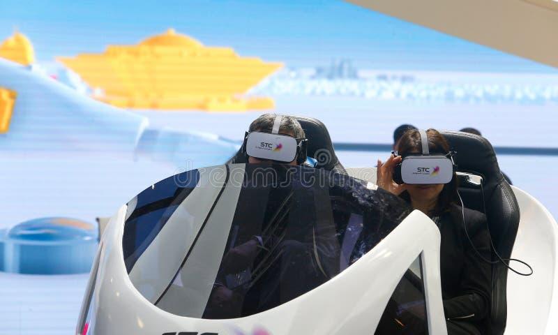 Visitantes que prueban experiencia del abejón de VR en la cabina de la STC en MWC 2019 de par en par imagen de archivo