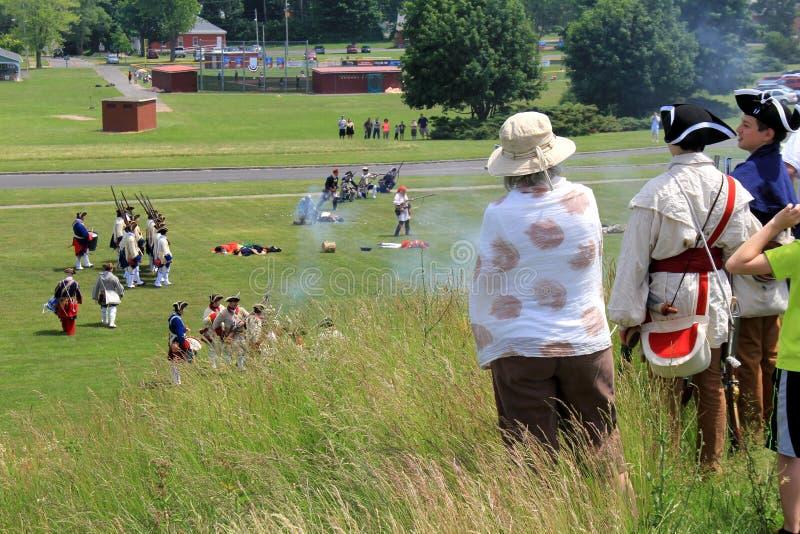 Visitantes que se colocan encima de una colina, mirando las reconstrucciones francesa y de indio de la guerra, fuerte Ontario, Nu foto de archivo
