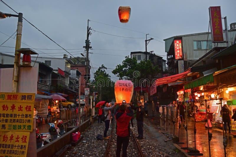 Visitantes que tomam imagens ao liberar a lanterna no céu em um dia chuvoso em ruas velhas de Shifen no final da noite foto de stock