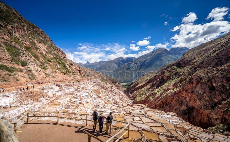 Visitantes que ven las cacerolas de la extracción de la sal en Perú fotos de archivo