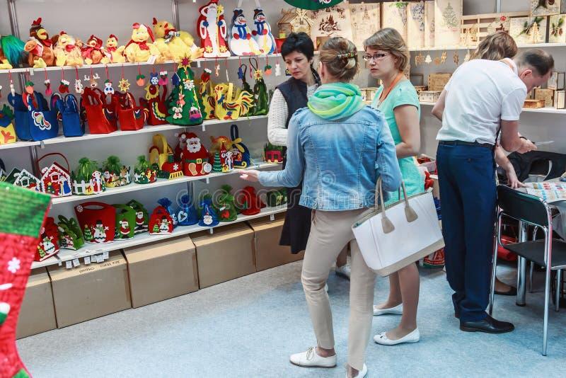 Visitantes y expositores que visitan los soportes y los objetos expuestos en imágenes de archivo libres de regalías