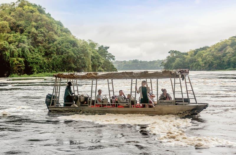 Visite de touristes le Murchison Falls sur le Nil blanc, Ugand images stock