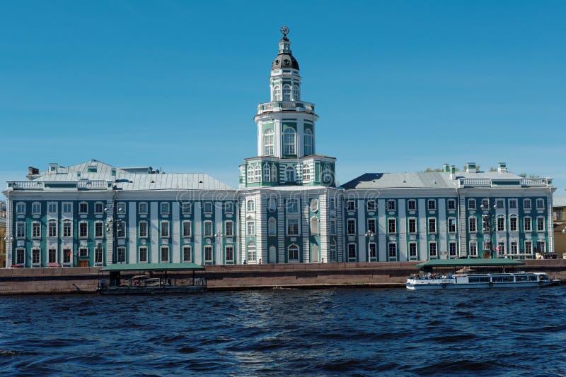 Visite o barco contra a construção de Kunstkamera em St Petersburg, Rússia fotografia de stock