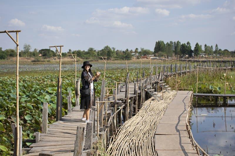 Visite thaïlandaise de voyage de personnes de femmes et portrait de pose pour la photo de prise sur le long pont en bois de Kae D image stock