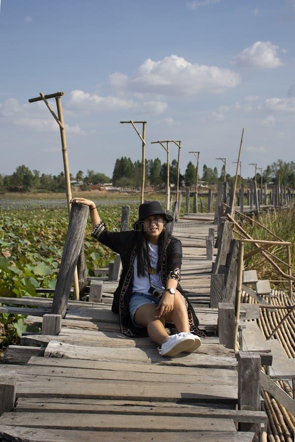 Visite thaïlandaise de voyage de personnes de femmes et portrait de pose pour la photo de prise sur le long pont en bois de Kae D photos stock
