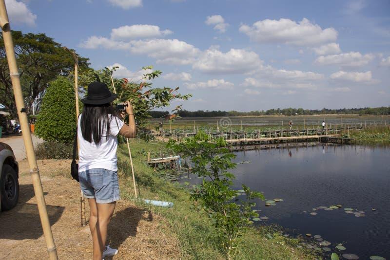 Visite thaïlandaise de voyage de personnes de femmes et portrait de pose pour la photo de prise sur le long pont en bois de Kae D photographie stock libre de droits